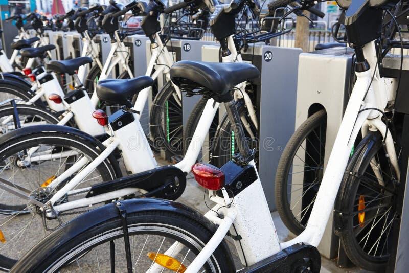Bicicletas urbanas de carregamento da bateria elétrica na cidade mobilidade fotos de stock