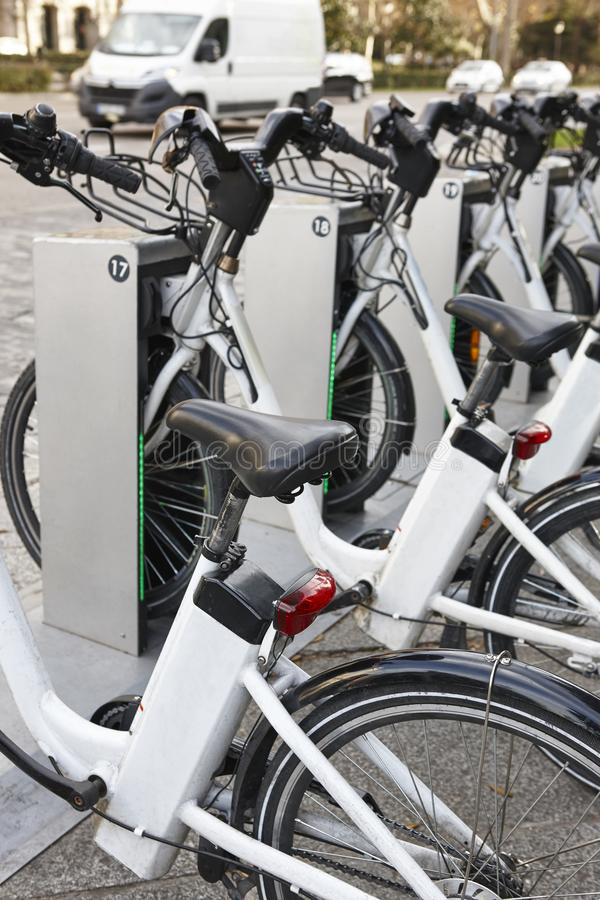 Bicicletas urbanas de carregamento da bateria elétrica na cidade Transporte de Eco imagens de stock