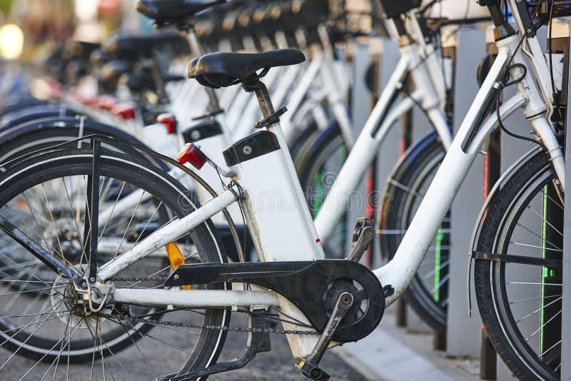 Bicicletas urbanas de carregamento da bateria el?trica na cidade Transporte de Eco fotos de stock royalty free