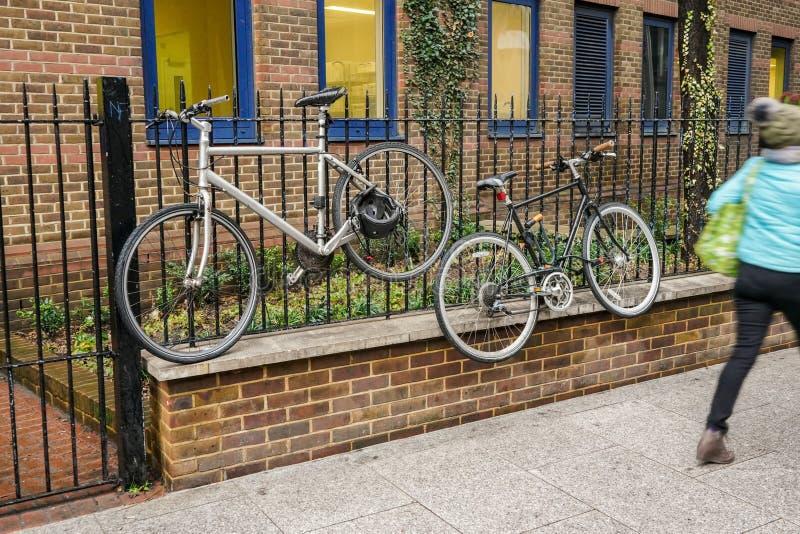 Bicicletas velhas travadas à cerca do metal, alta acima da pessoa à terra, borrada que passa perto no pavimento foto de stock