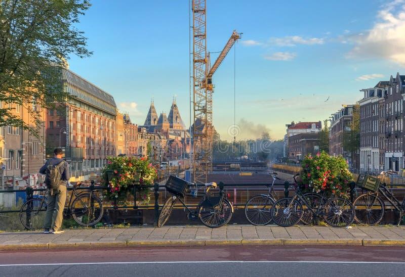 Bicicletas y flores en el puente de Amsterdam, mirando en la dirección o foto de archivo