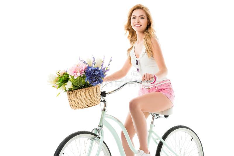 Bicicletta attraente di guida della giovane donna con la merce nel carrello dei fiori fotografia stock libera da diritti
