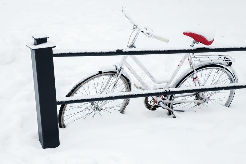 Bicicletta bianca parcheggiata in cumulo di neve fotografia stock libera da diritti