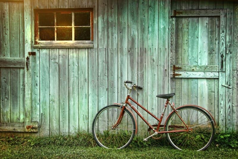 Bicicletta che si appoggia contro il granaio grungy fotografia stock libera da diritti