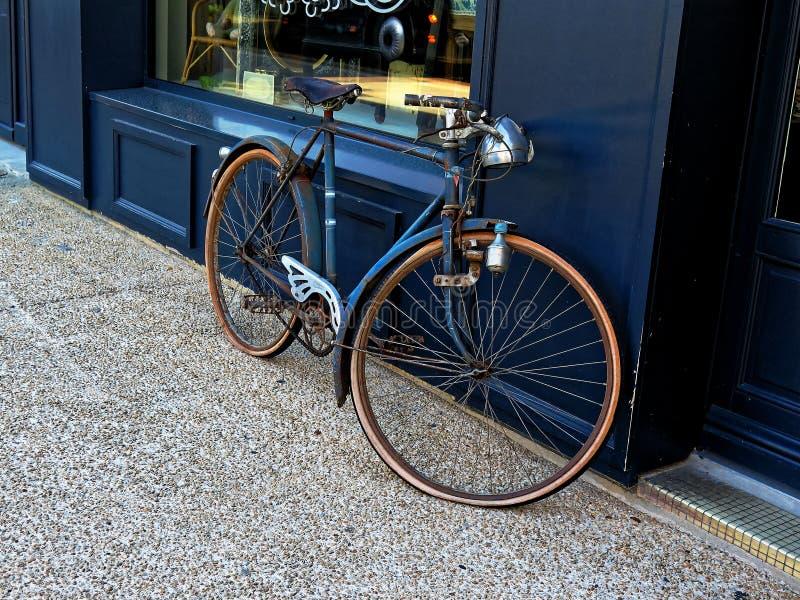 Bicicletta d'annata che pende contro una finestra del negozio fotografia stock
