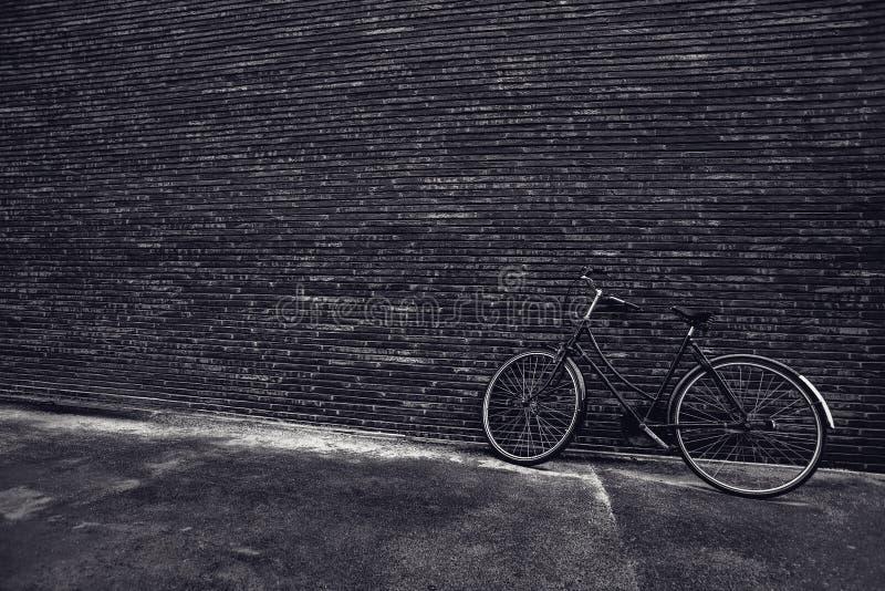 Bicicletta d'annata classica dei pantaloni a vita bassa che pende contro la parete della via fotografie stock
