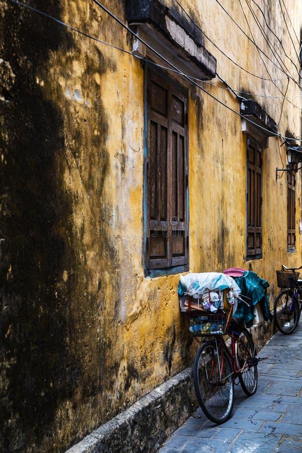 Bicicletta d'annata da una parete antica gialla di vecchia costruzione nella città antica di Hoi An, Vietnam Verticale, vista del immagine stock