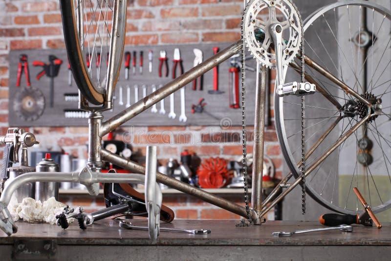 Bicicletta d'epoca in officina in garage sul banco di lavoro con attrezzi, concetto didattico immagine stock libera da diritti