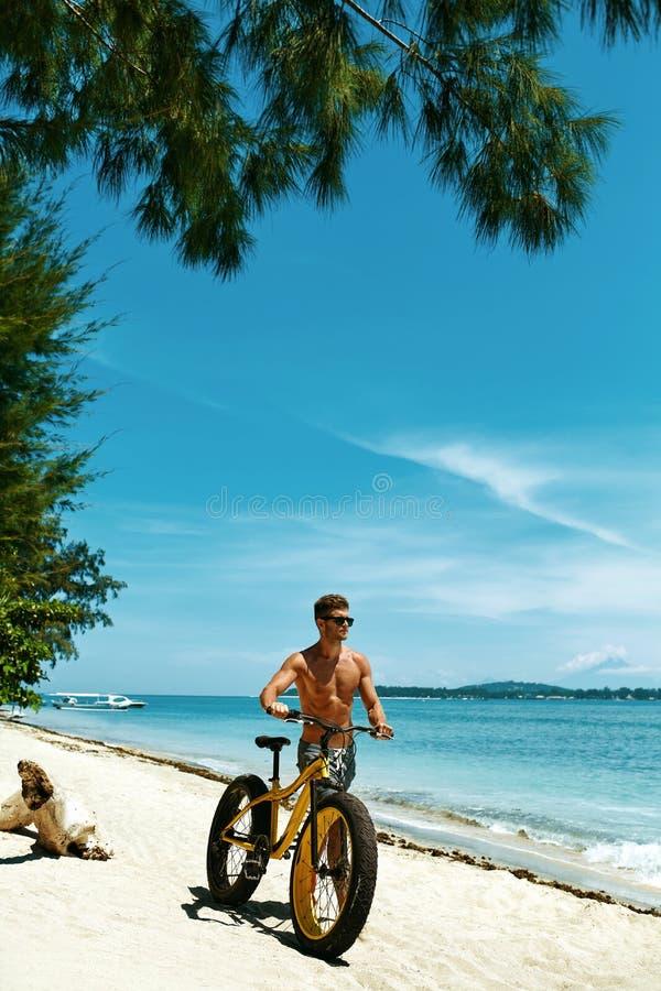 Bicicletta della sabbia di guida dell'uomo sulla spiaggia Attività di sport di estate fotografia stock