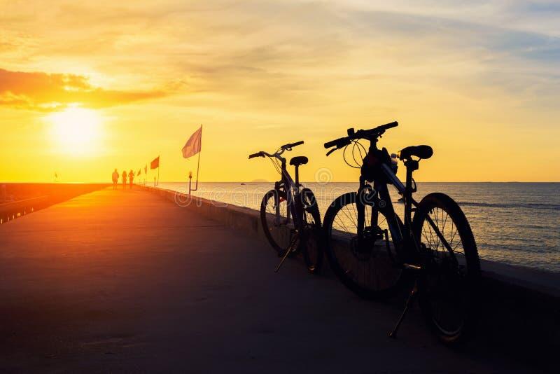 Bicicletta della siluetta con bello paesaggio al tramonto immagini stock libere da diritti