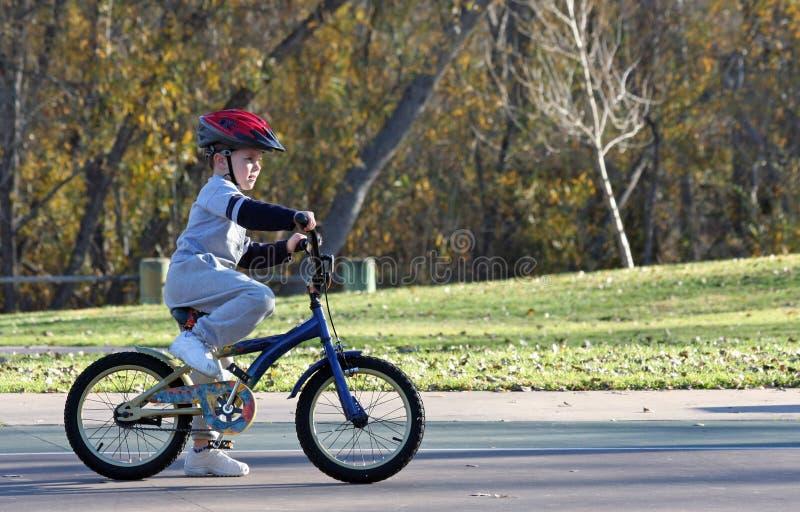 Bicicletta di guida del ragazzo alla sosta fotografia stock