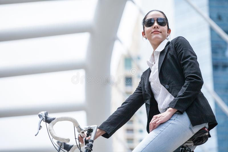 Bicicletta di guida della donna di affari da lavorare alla via urbana trasporto e sano astuto fresco di stile di vita di modo immagini stock libere da diritti
