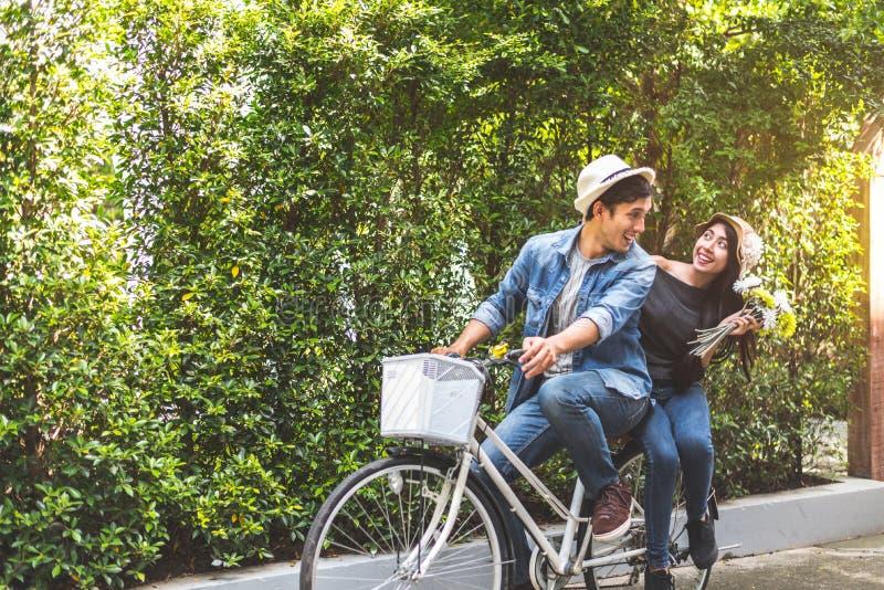 Bicicletta di guida delle coppie felici insieme nel fondo romantico del parco di vista San Valentino e concetto di luna di miele  immagine stock