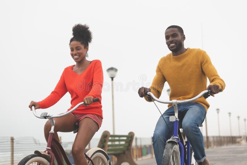 Bicicletta di guida delle coppie a passeggiata un giorno soleggiato immagini stock libere da diritti
