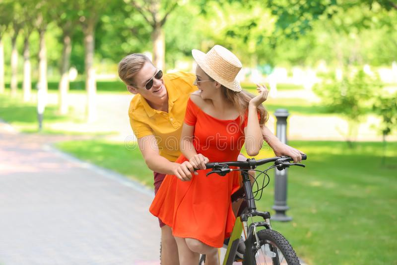 Bicicletta di guida delle giovani coppie in parco immagine stock libera da diritti