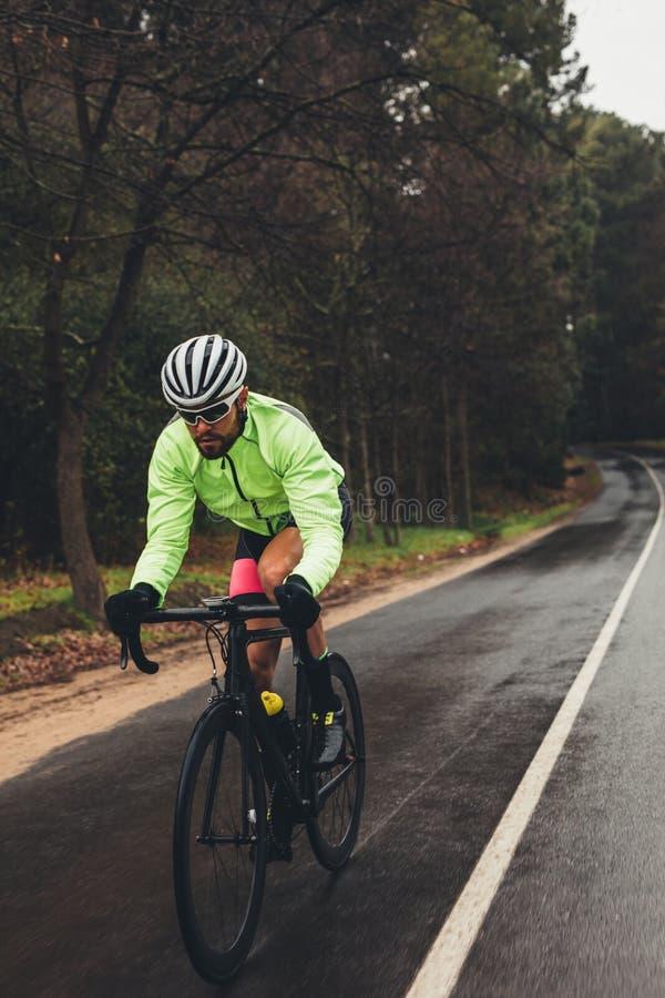 Bicicletta di guida dello sportivo sulla strada principale del paese fotografia stock libera da diritti