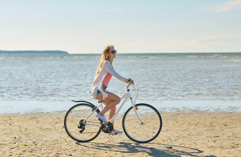 Bicicletta felice di guida della donna lungo la spiaggia di estate fotografie stock libere da diritti
