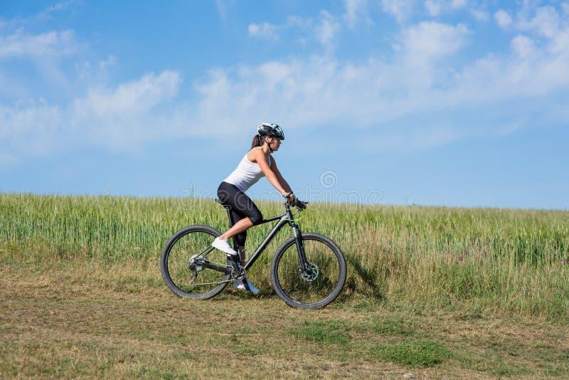 Bicicletta felice di guida della giovane donna all'esterno fotografia stock