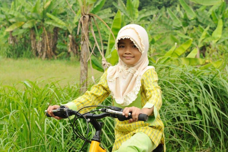 Bicicletta musulmana di guida della ragazza fotografia stock libera da diritti