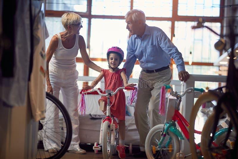 Bicicletta nuova di compera dei nonni per poco bambino fotografie stock libere da diritti
