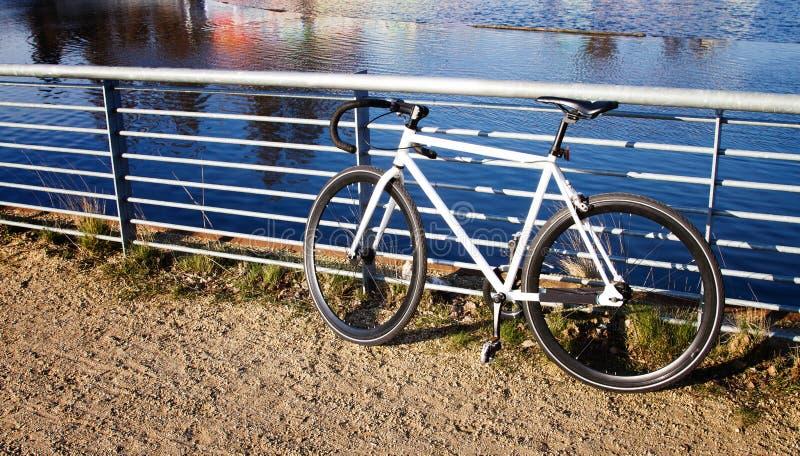 Bicicletta parcheggiata contro le rotaie che trascurano un canale fotografia stock