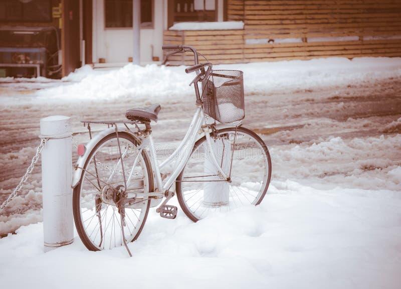Bicicletta parcheggiata nella scena di inverno immagine stock