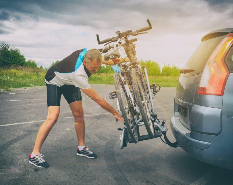 Biciclette di caricamento dell'uomo sullo scaffale della bici fotografie stock libere da diritti