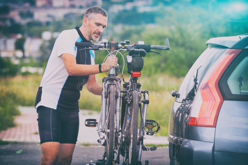 Biciclette di caricamento dell'uomo sullo scaffale della bici immagini stock