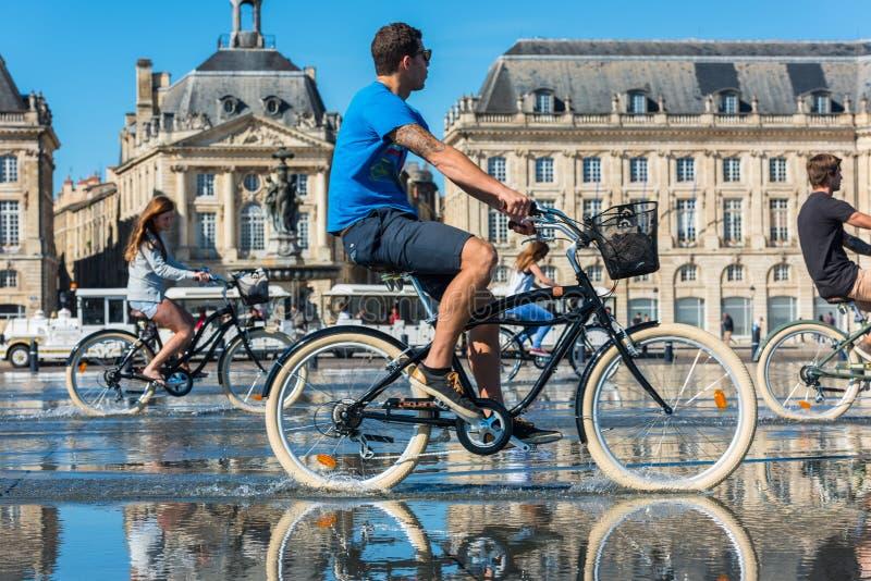 Biciclette di guida della gente nella fontana in Bordeaux, Francia immagini stock libere da diritti