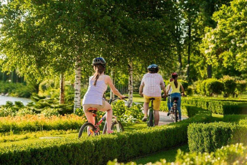 Biciclette di guida della gente, vista posteriore immagine stock