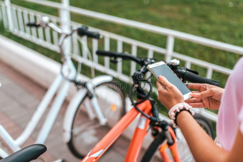 In biciclette di parcheggio del fondo della città dell'estate, la ragazza sceglie l'applicazione dell'itinerario, telefono della  immagini stock