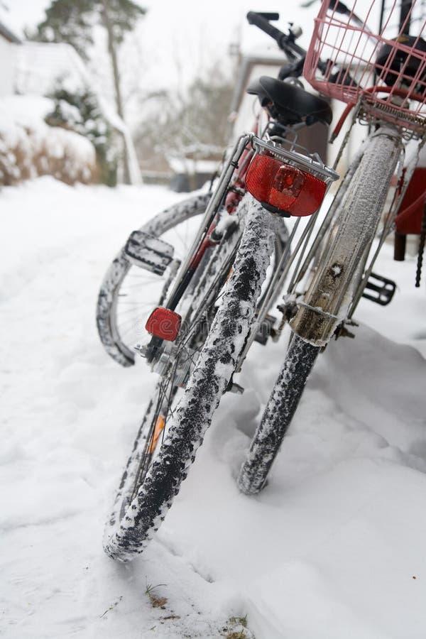 Biciclette parcheggiate in un cumulo di neve fotografia stock libera da diritti