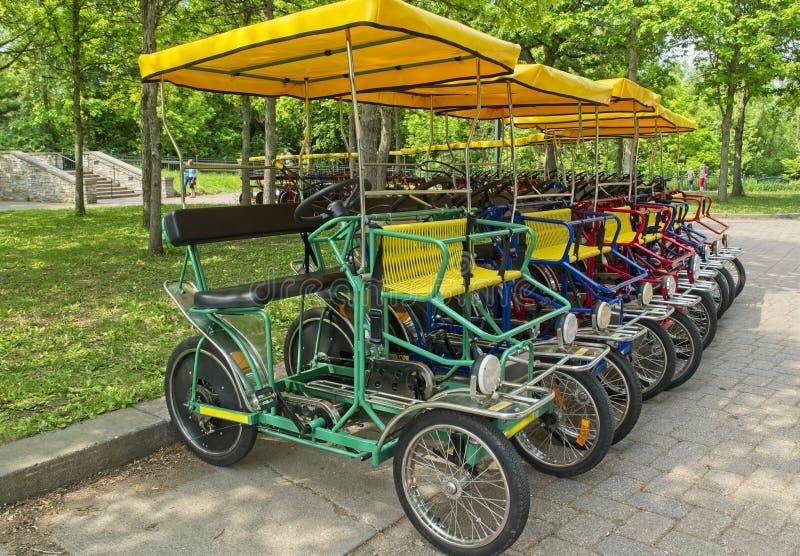 Bicis de cuatro ruedas de alquiler en el parque foto de archivo