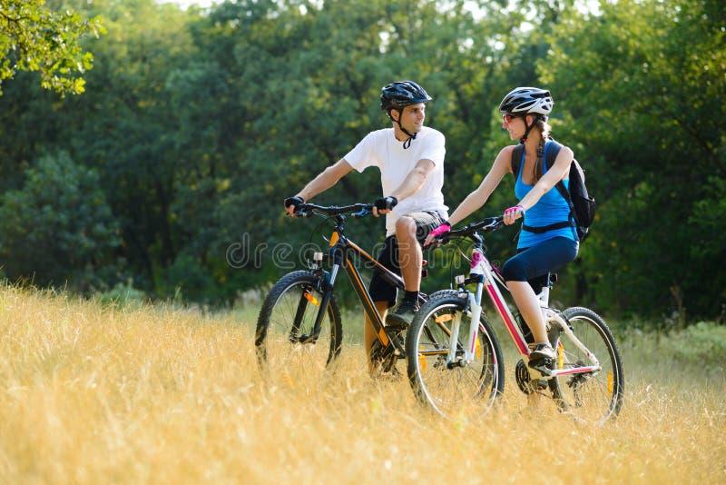 Bicis de montaña felices jovenes del montar a caballo de los pares al aire libre imagen de archivo libre de regalías