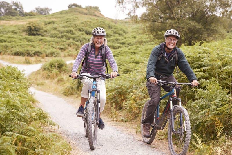 Bicis de montaña mayores del montar a caballo de los pares en un carril del país durante una acampada que sonríe, vista delantera fotos de archivo libres de regalías