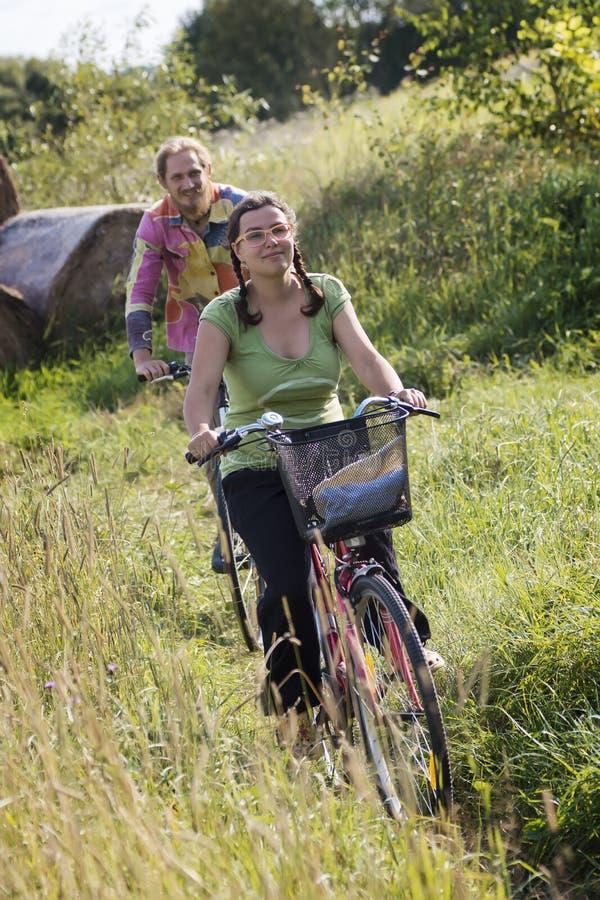 Bicis del montar a caballo de los pares en campo imagen de archivo libre de regalías