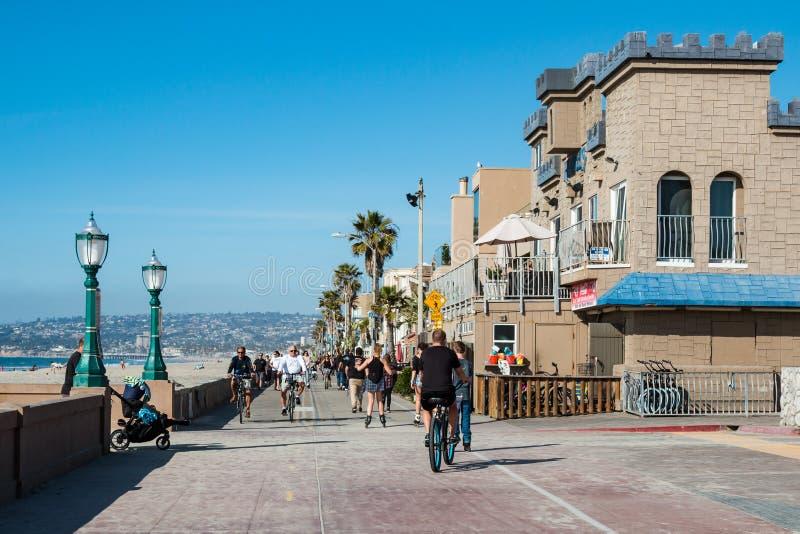 Bicis del paseo de la gente en paseo marítimo de la playa de la misión en San Diego fotografía de archivo libre de regalías