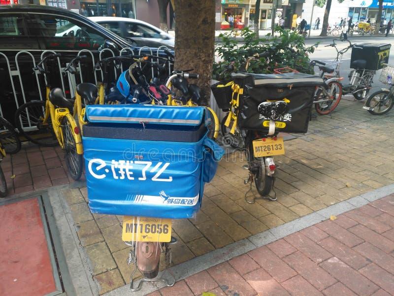 Bicis eléctricas con e le yo y casos de la entrega de la comida de Meituan que parquean en la calle Entrega de la comida fotos de archivo