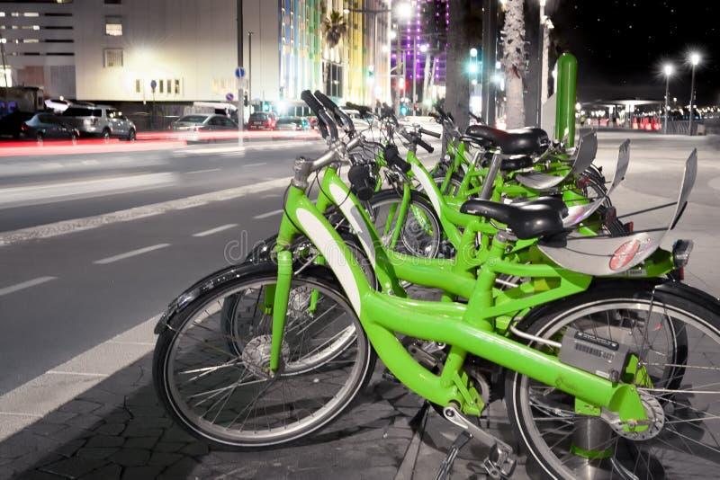 Bicis verdes parqueadas - calle de la ciudad en la noche imagen de archivo libre de regalías