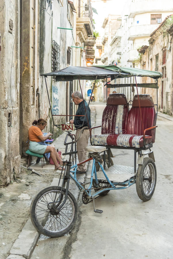 Bicitaxi driver buying morning coffee Havana stock photography