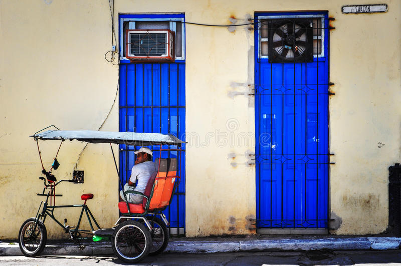 Bicitaxi driver parked up, infront of two blue doors, in the shade taking a rest. This Cuban bicycle taxi driver is parked up in the shade, waiting for a fare stock photography