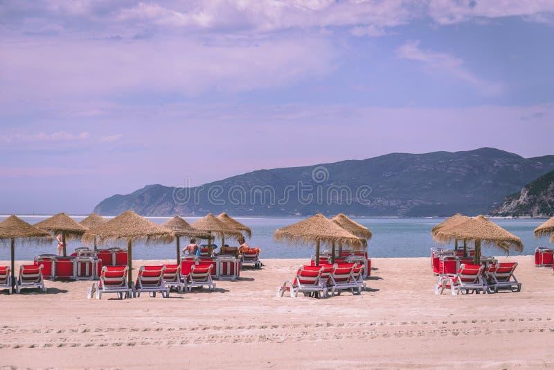 Bico das Lulas plaża, Troia, Portugalia - słomiani parasole i krzesła przy piaskowatą plażą zdjęcie stock