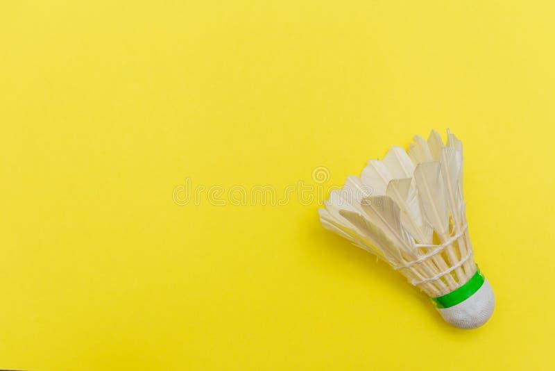 Bico-obturador de Badminton ou birdie em um plano plano amarelo sólido que simboliza esportes e atividades com espaço para cópia fotos de stock royalty free