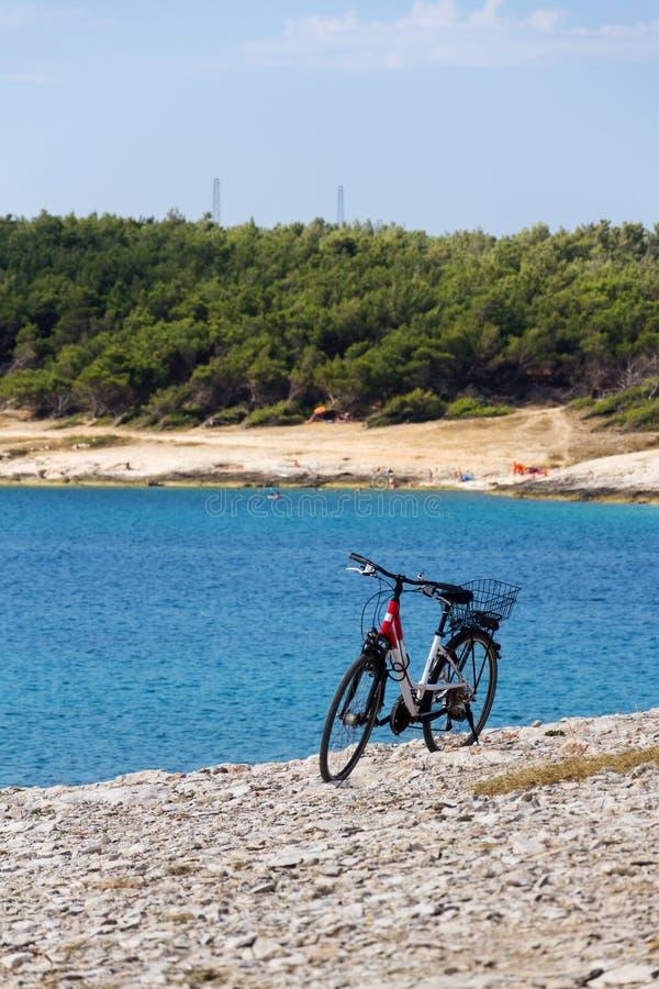 Bicycle на каменистом пляже, полуострове Kamenjak, Адриатическом море, Premantura, Хорватии стоковые фотографии rf