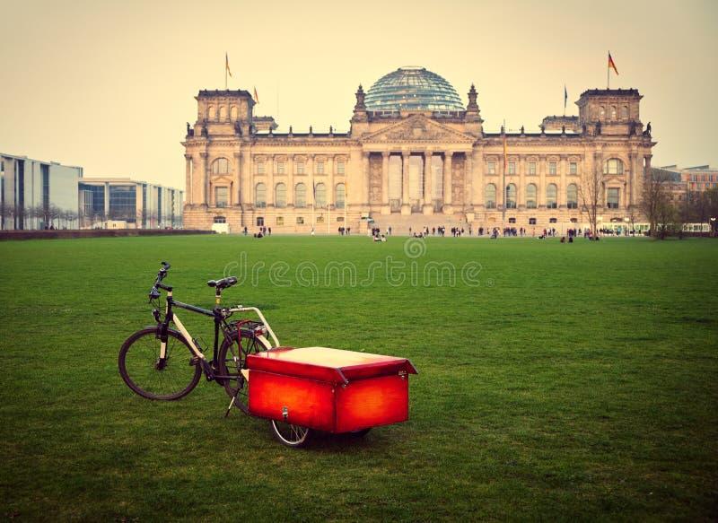 Bicycle с красной коробкой против здания Reichstag в Берлине стоковые фотографии rf