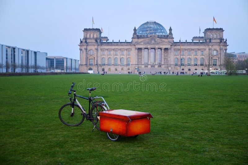 Bicycle с красной коробкой против здания Reichstag в Берлине стоковое фото