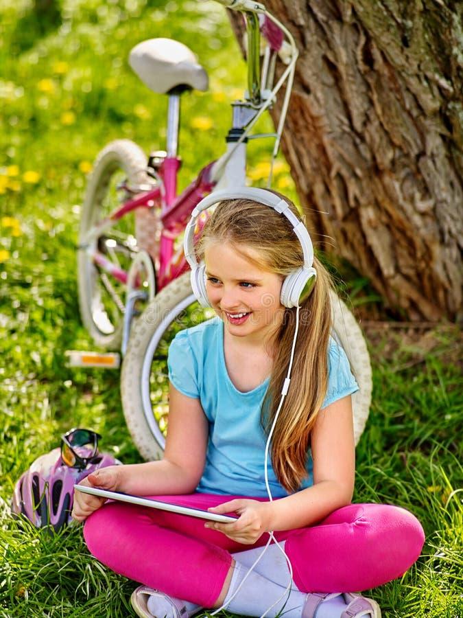 Bicycle шлемофон девушки нося наблюдая на ПК таблетки стоковое изображение