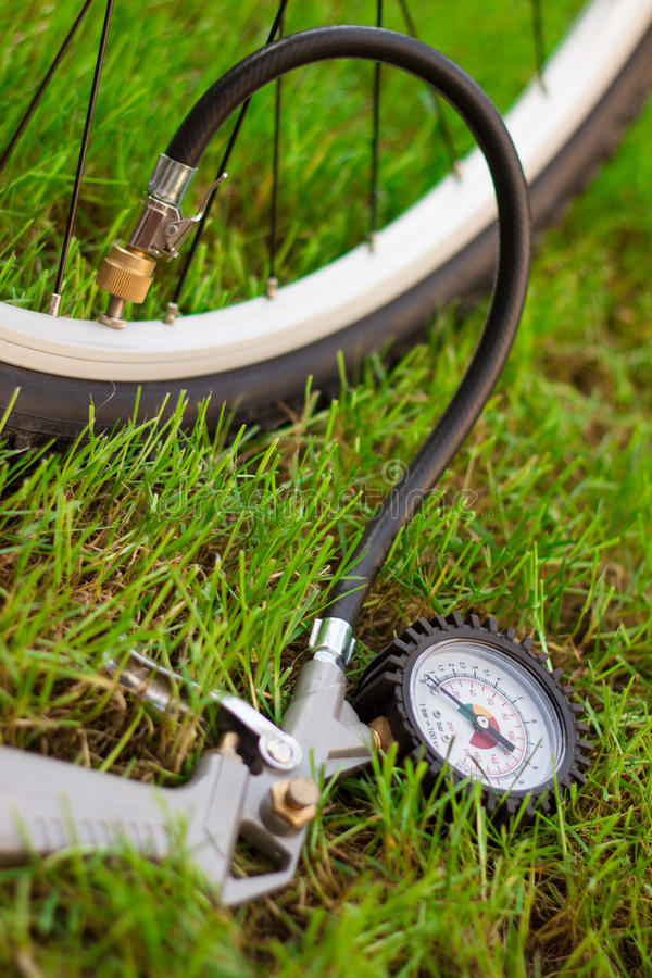 Bicycle and air compressor. Fresh photo of bicycle wheel with air compressor in grass stock image