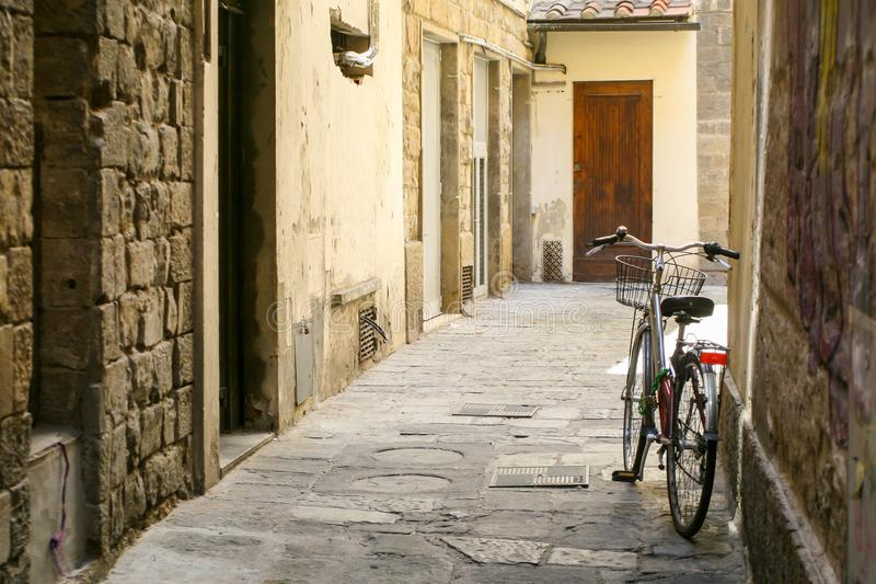 A bicycle with a basket on a narrow European street. Stone houses. stock images