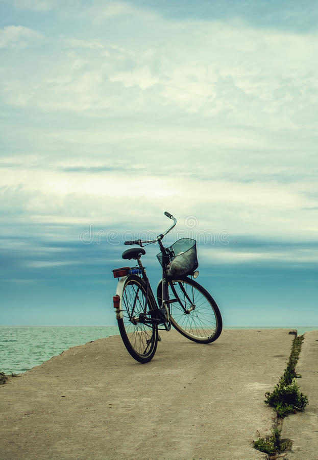 Bicycle at the beach on cloudy sky background. vintage retro sty. Bicycle at the beach on concrete pier on cloudy sky background. vintage retro styled royalty free stock image